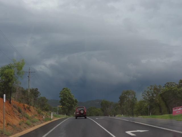 Car driving toward ominous thunderstorm clouds